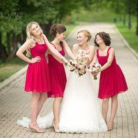 Невеста в длинном платье со шлейфом и подружки с букетиками в красных платьях миди на широких бретельках, расклешенным низом и бежевых туфельках  на парковой аллее