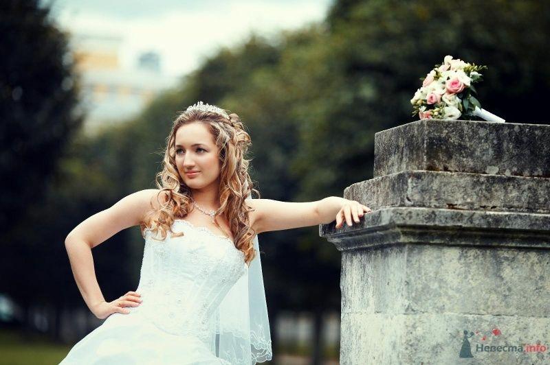 Невеста в белом платье стоит возле серой стены на фоне леса