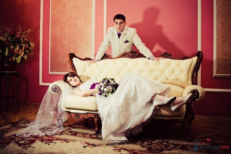 Невеста лежит на бежевом диване, а рядом стоит жених - фото 47663 sofiya