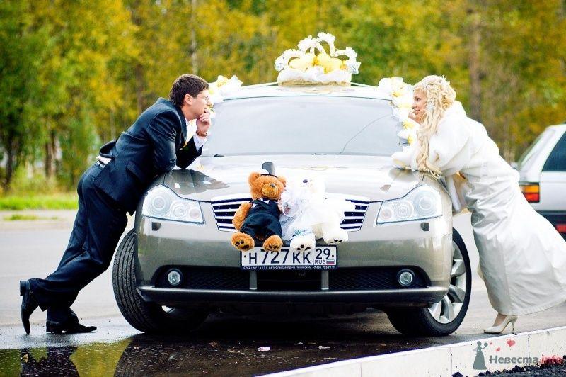 Жених и невеста стоят возле серой машины и смотрят друг на друга