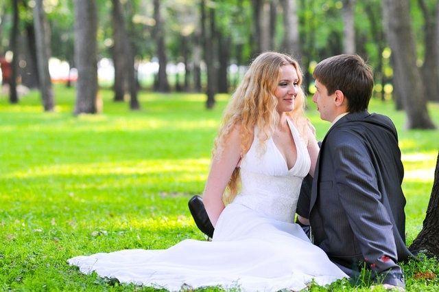 Жених и невеста, прислонившись друг к другу, сидят на фоне деревьев