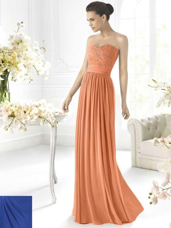 """Подружка невесты в длинном в пол оранжевом платье с корсетом, драпировкой, вырезом """"сердечко"""" стоит у стола - фото 579405 La Promesa свадебный бутик - испанские платья"""