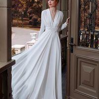 Модель EMSE 0230 молочного цвета Вечернее платье длиной пол с глубоким V-образным вырезом на запахе. Рукава покроя «кимоно» , заужены к низу, длиной до запястья. На лифе и спинке оформлены сборки. Юбка имеет большое расширение к низу, пояс декорирован бло
