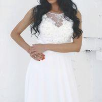 Скромное шифоновое платье молочного цвета.Полупрозрачный верх украшен воздушными кружевами и жемчужным бисером.Открытые рукава подчеркнут изящные ручки невесты.  Платье отлично подойдет для свадебной церемонии как на пляже,так и в городе