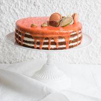 Милый торт с цитрусовой глазурью. украшенный экзотическими фруктами и сладостями