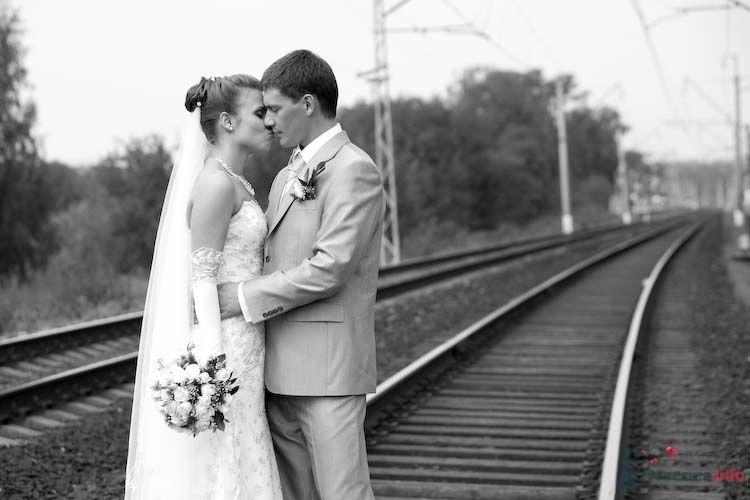 Жених и невеста, прислонившись друг к другу, стоят на железнодорожной