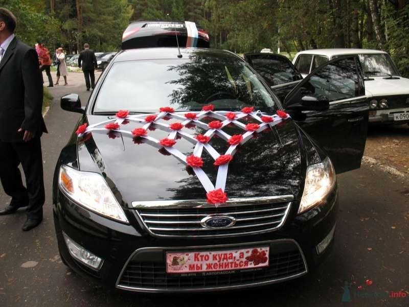 Черный автомобиль украшенный сеткой из белого фатина и красными искусственными красными розами на капоте. - фото 25740 Dexter