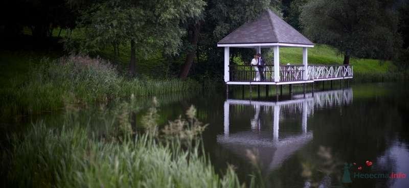 Жених и невеста стоят, прислонившись друг к другу, у озера в беседке - фото 52166 daisy82