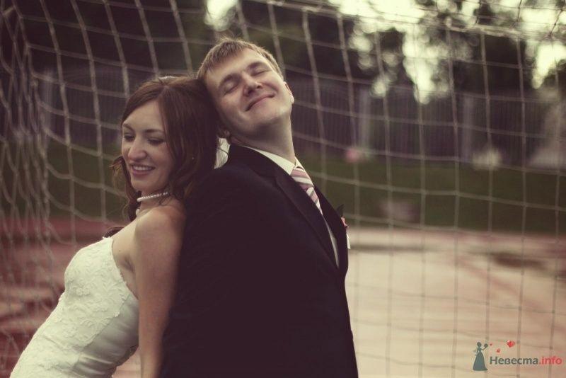 Жених и невеста стоят, прислонившись друг к другу, на фоне прозрачной сетки - фото 45818 Tane4ka