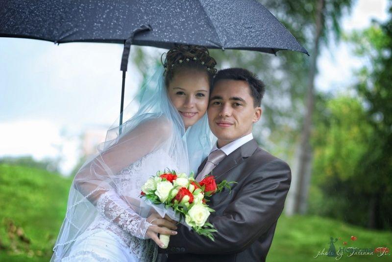 Жених и невеста стоят, прислонившись друг к другу, на фоне зелени под зонтом - фото 45507 KartInka