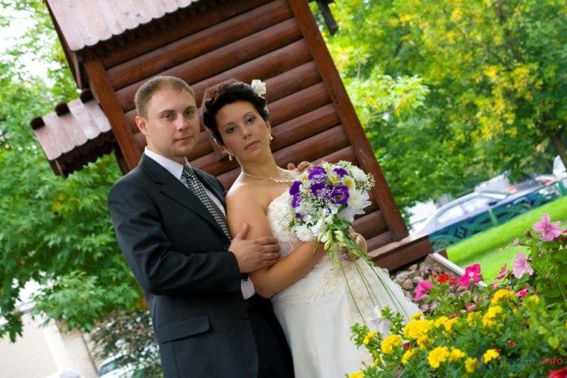 Жених и невеста стоят, прислонившись друг к другу, на фоне деревянного домика - фото 40475 Ксюньчик