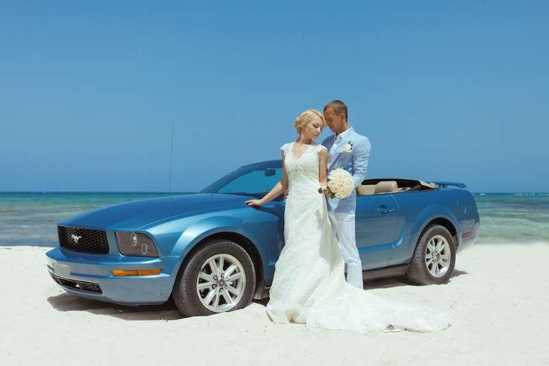 На побережье на фоне синего кабриолета стоит влюбленная пара, невеста в белом платье со шлейфом держит руку на капоте, позади - фото 3054961 Caribbean Wedding - свадьба в Доминикане
