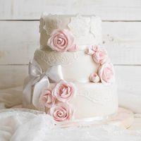 Элегантный свадебный торт, декорированный кружевом и розовыми розами.