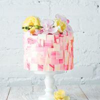 Не большой свадебный торт ,украшенный тончайшими пластиночками из белого шоколада и яркой композицией из живых цветов