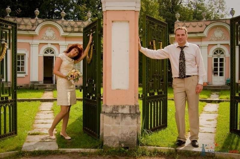 Жених и невеста стоят ворот розового здания - фото 43068 Рыжий Катенок