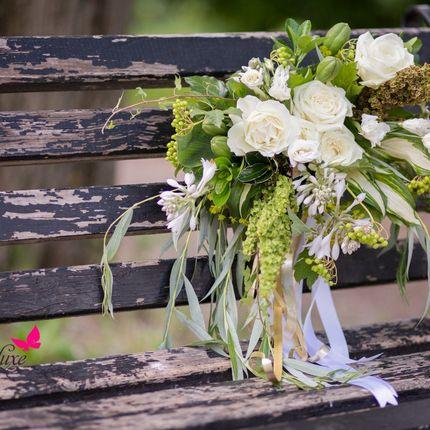 Букет невесты из роз, эустомы, ягод и зелени.