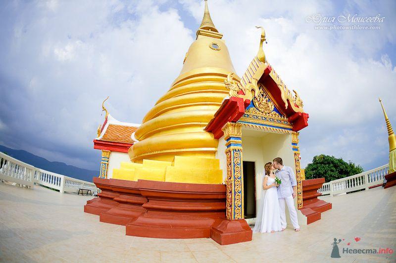 Жених и невеста, прислонившись друг к другу, стоят на фоне домака