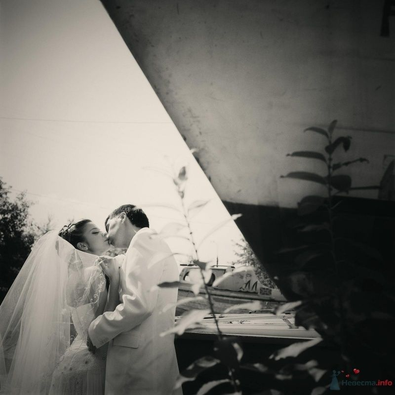 Жених и невеста целуются на фоне корабля