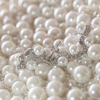 Посеребренные украшения для невесты - длинные изогнутые серьги с кристаллами и жемчугом.