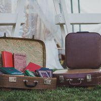 Чемоданчики с книжками и чемодан для бонбоньерок рядом со стилизованной стремянкой