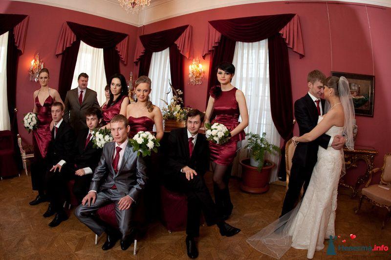 Жених в черном костюме, красном галстуке обнимает невесту в белом