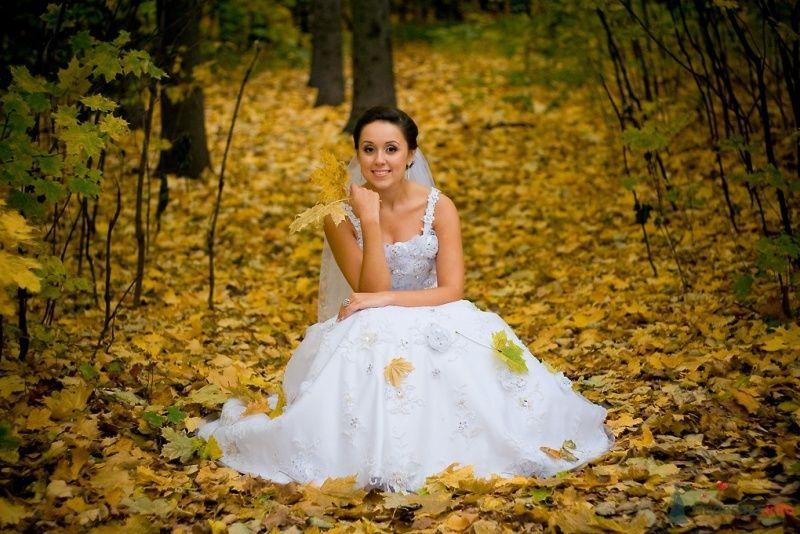 Невеста в длинном белом платье сидит в осеннем лесу