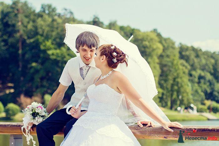 Молодожены под свадебным зонтом