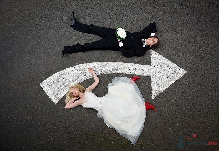 Жених и невеста лежат на земле, где нарисованна белая стрелка