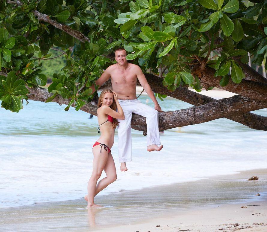 На побережье отдыхают влюбленные, парень в белых брюках сидит на ветке тропического дерева, девушка в красном купальнике стоит - фото 2258346 Свадебный фотограф Марина Лонгортова