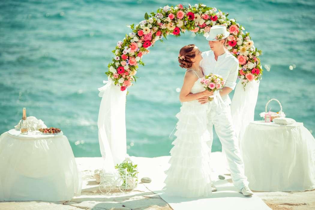 На фоне лазурного океана под сводом свадебной арки, украшенной белой тканью и цветами, стоят молодожены, жених в белых брюках, - фото 2818579 Sunny Cyprus Wedding